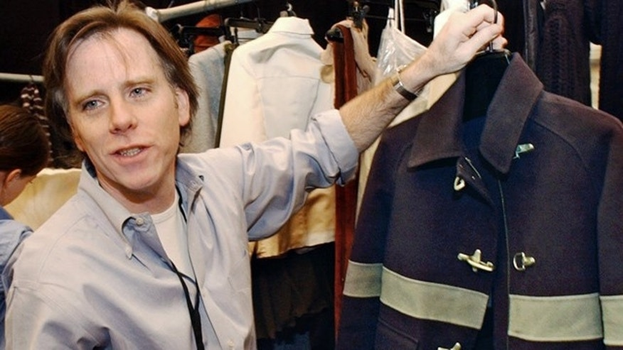 In this Feb. 11, 2002 file photo, designer Charles Nolan shows a black and steel blue wool hip-length coat resembling a fireman's coat from his Anne Klein fall-winter 2002 collection, to his father, Phil Nolan, a former Hempstead, N.Y. firefighter, backstage before the show in New York. Nolan, known to have a passion for American classics but skew them with a modern edge and personal touch, died Sunday, Jan. 30, 2011.