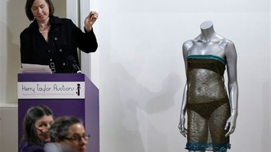 March 17: The auctioneer hammers down to close the sale of the see-through knitted lace dress worn by Kate Middleton on display, right, during the 'Passion for Fashion' auction in central London. (AP)