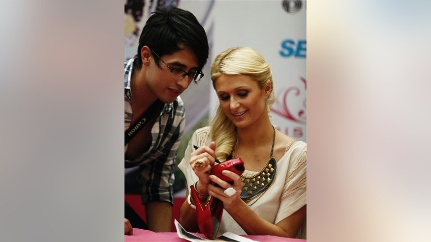 Paris Hilton autographs the bottom of a high-heeled shoe during her autograph signing session at a Sears in the Perisur Mall of Mexico City, Mexico, Tuesday March 29, 2011. Hilton is in Mexico to promote her new shoe line.  (AP Photo/Eduardo Verdugo)
