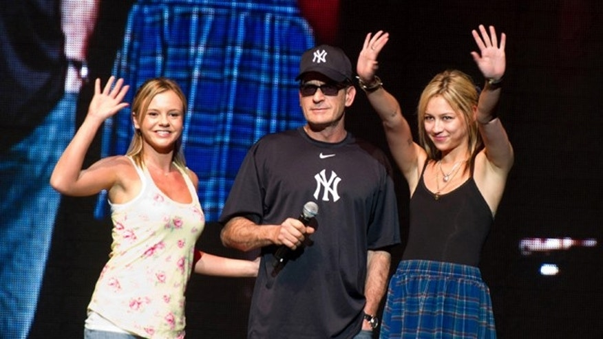 "Charlie Sheen appears onstage with his ""Goddesses"" Natalie Kenley, right, and Rachel Oberlin at his Violent Torpedo of Truth show at Radio City Music Hall in New York."