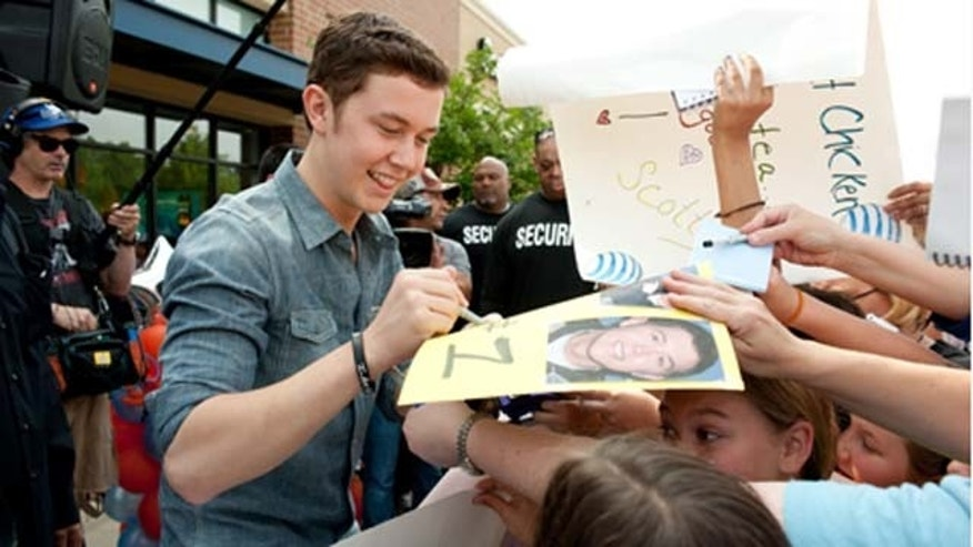 """GARNER, NC - MAY 14: """"American Idol"""" finalist Scotty McCreery greets fans at an AT&T store May 14, 2011 in Garner, North Carolina during a homecoming tour. In the past six weeks, McCreery has gone from being a cashier at Lowes Foods and a singer known only around the Triangle to being a national if not global phenomenon on """"American Idol."""" Residence and town officials prepared a hometown hero's welcome for McCreery two days after he advanced to become one of three top finalist in season ten of America Idol. (Photo by Steve Exum/Getty Images)"""