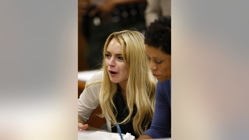 Actress Lindsay Lohan reacts beside her attorney Shawn Chapman Holley (R) as Judge Marsha Revel rules that Lohan had violated her probation on a 2007 drunken driving charge in Beverly Hills, California July 6, 2010. Lohan was sentenced to 90 days in jail on Tuesday after the Beverly Hills judge ruled that she had violated her probation by missing a string of alcohol education classes imposed for a 2007 drunk driving arrest. REUTERS/David McNew/Pool (UNITED STATES - Tags: ENTERTAINMENT CRIME LAW)