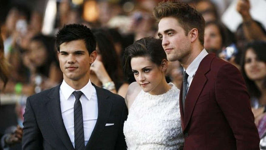 June 24: 'Twilight' stars Taylor Lautner, Kristen Stewart and Robert Pattinson pose for cameras at the premiere of the film.