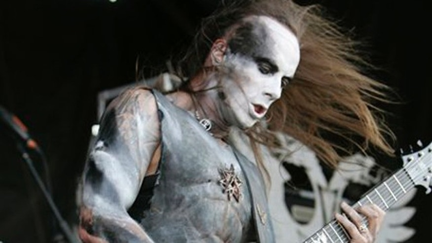 "FILE - In this Aug. 4, 2009 file photo Adam Darski, frontman for the Polish death metal band Behemoth, is shown in concert at the 2009 Rock Star Energy Drink Mayhem Festival at the Comcast Center in Mansfield, Mass. A judge in Gdynia, Poland, found Darski innocent on Thursday, Aug. 17, 2011, of offending religious feelings, ruling that his ripping up of a Bible during a 2007 show was a form of artistic expression consistent with the style of his band. Darski, who uses the stage name Nergal, also called the Bible ""a deceitful book"" _ strong language in his predominantly Roman Catholic country. (AP Photo/Robert E. Klein, file)"