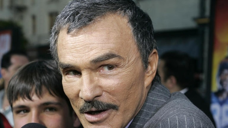 "Actor Burt Reynolds, right, who stars in the movie  ""The Longest Yard"", gets interviewed after arriving for the movie's world premiere, Thursday, May 19, 2005, in the Hollywood portion of Los Angeles. Reynolds' son Quinton Reynolds looks on from left. (AP Photo/Danny Moloshok)"