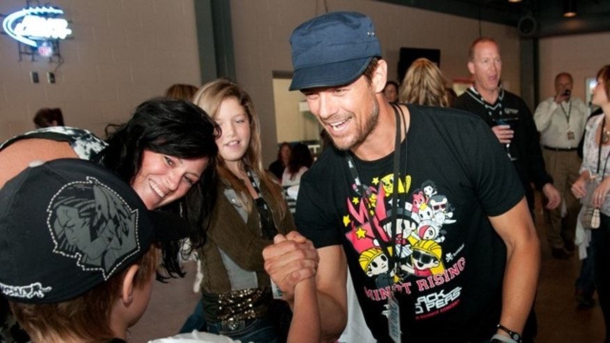 "Sept. 3: Josh Duhamel shakes hands with Owen Hanson as Tasha Hanson, second left, and Olivia Hanson look on at the North Dakota State Fairgrounds in Minot, N.D. Tasha Hanson said she grew up with Josh and he is ""like family."""
