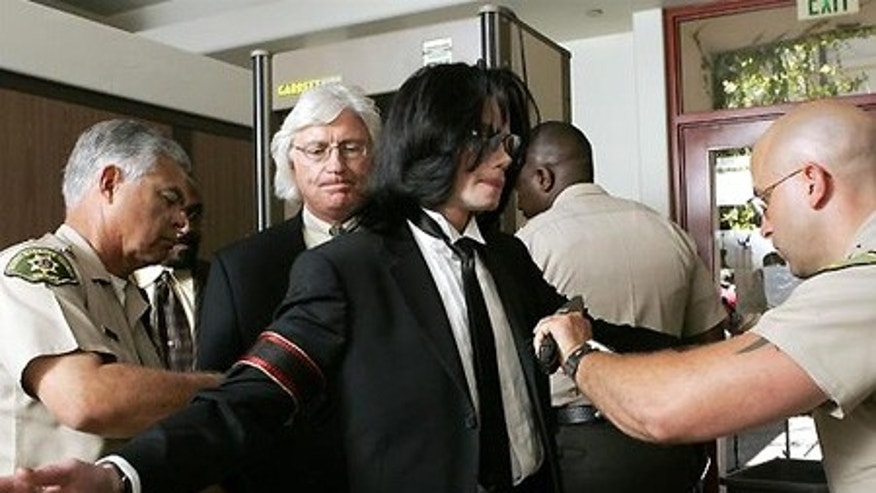 Michael Jackson goes through security as he arrives at Santa Barbara County Superior Court in Santa Maria, Calif., with his attorney Thomas  Mesereau Jr, behind Jackson, Monday, June 13, 2005. The jury in the Michael Jackson trial reached a verdict Monday in the child molestation case. (AP Photo/Kevork Djansezian )