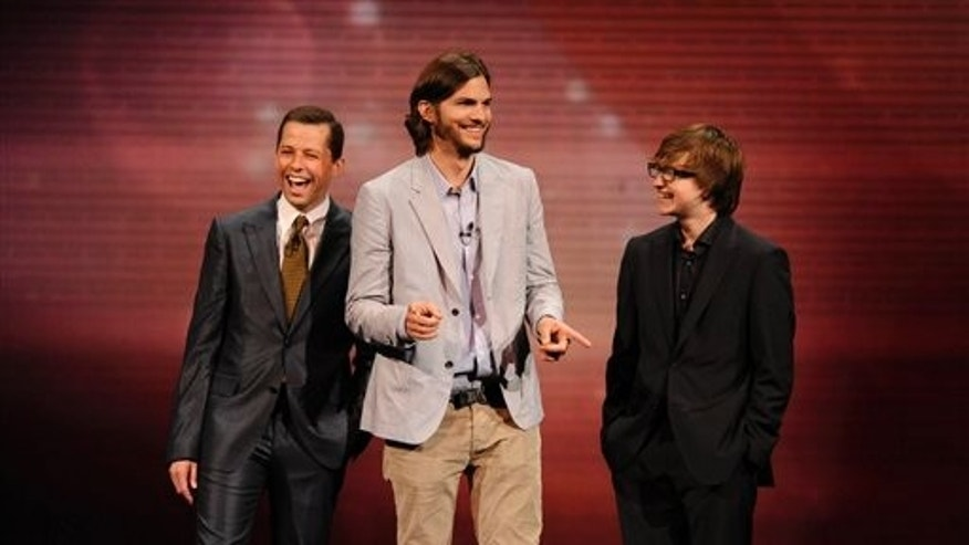 """In this May 18, 2011 file publicity image released by CBS, the cast of """"Two and a Half Men,"""" from left, Jon Cryer, Ashton Kutcher, and Angus T. Jones are shown during their presentation at CBS' Upfronts (AP)"""