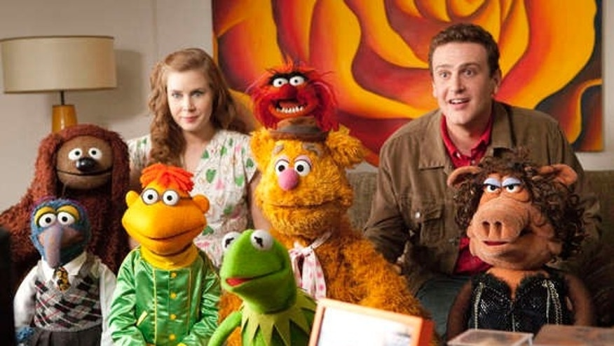 "In this film publicity image released by Disney, Amy Adams, left, and Jason Segel are shown with the muppet characters in a scene from ""The Muppets."" (AP Photo/Disney Enterprises, Patrick Wymore)"