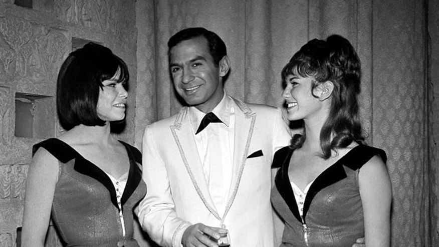 """In this 1965 file photo, actor Ben Gazzara poses with dancers Sandy Garrett, left, and Victoria Scruton while filming an episode of the TV series """"Run for Your Life,"""" in Los Angeles."""