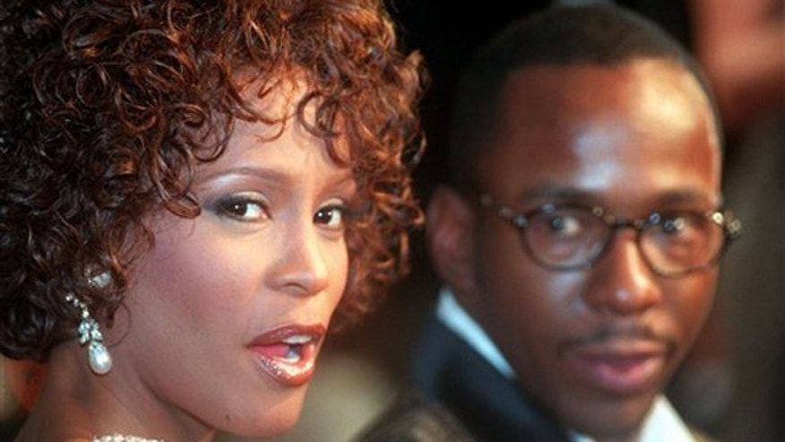 "FILE - In this Oct. 13, 1997 file photo, Whitney Houston looks over her shoulder as her husband Bobby Brown looks to her at the premiere of ""The Wonderful World of Disney"" movie ""Cinderella,"" at Mann's Chinese Theater in the Hollywood section of Los Angeles, Whitney Houston, who reigned as pop music's queen until her majestic voice and regal image were ravaged by drug use, has died, Saturday, Feb. 11, 2012. She was 48. (AP Photo/Rene Macura, File)"