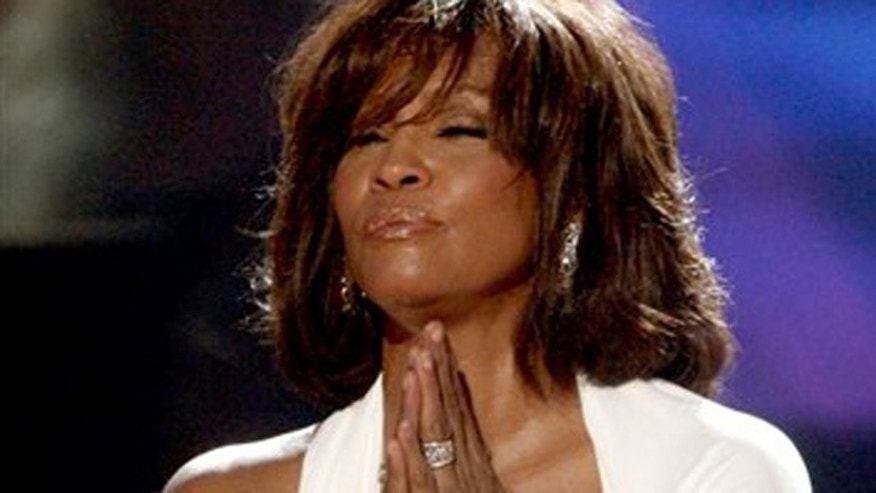 FILE - In this Nov. 22, 2009, file photo, singer Whitney Houston receives the International Artist Award onstage at the 37th Annual  American Music Awards in Los Angeles. Houston, who reigned as pop music's queen until her majestic voice and regal image were ravaged by drug use, has died, Saturday, Feb. 11, 2012. She was 48. (AP Photo/Matt Sayles, File)