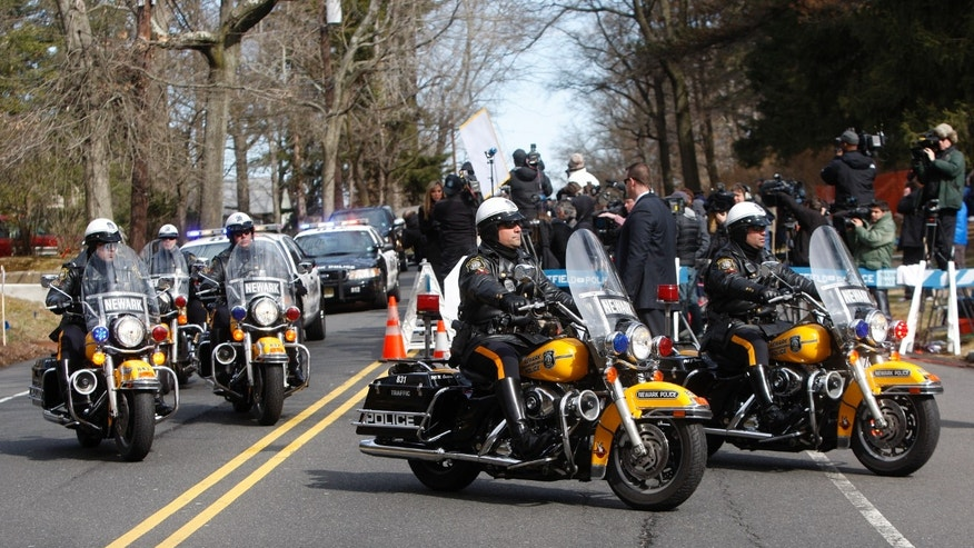 A Newark Police Department motorcade escorts the hearse carrying the body of Whitney Houston arrives at Fairview Cemetery for her burial in Westfield, N.J., on Sunday. (AP Photo/Rich Schultz)