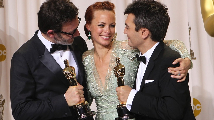"Michel Hazanavicius, left, poses with his award for best director for ""The Artist"" with his wife Bérénice Bejo, center, and producer Thomas Langmann with his best picture award for the film during the 84th Academy Awards on Sunday in the Hollywood section of Los Angeles. (AP Photo/Joel Ryan)"