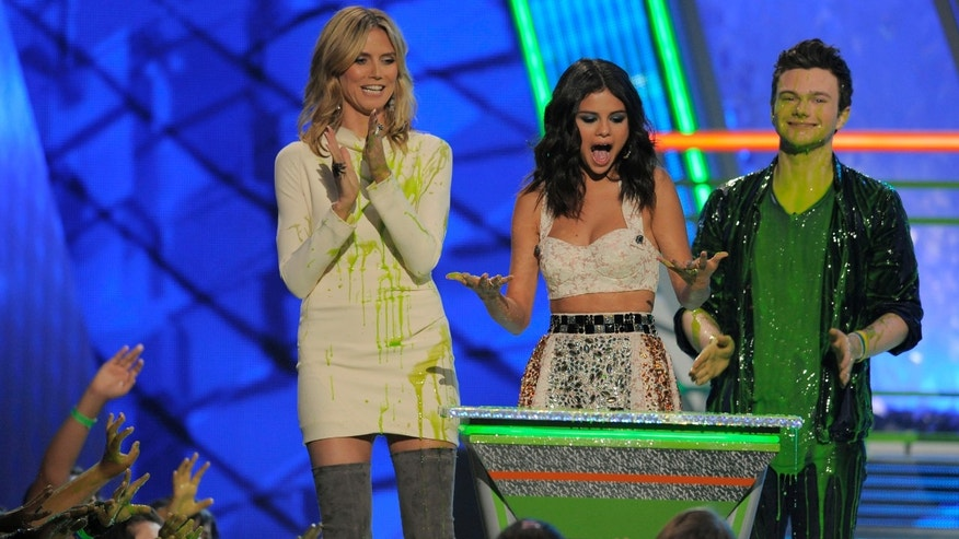 Heidi Klum, left, and Chris Colfer, right, present the favorite TV actress award to Selena Gomez onstage at Nickelodeon's 25th Annual Kids' Choice Awards on Saturday, March 31, 2012 in Los Angeles. (AP Photo/Chris Pizzello)
