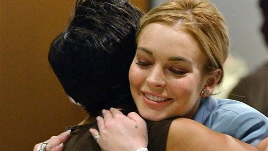 March 29, 2012: Lindsay Lohan, right, embraces her attorney, Shawn Chapman Holley after a progress report on her probation for theft charges at Los Angeles Superior Court.