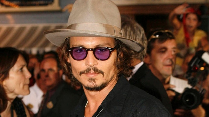 "Actor Johnny Depp poses for photographers at the film premiere of  ""Pirates of the Caribbean: Dead Man's Chest,"" at the Disneyland theme park in Anaheim, Calif., on Saturday, June 24, 2006. (AP Photo/Matt Sayles)"