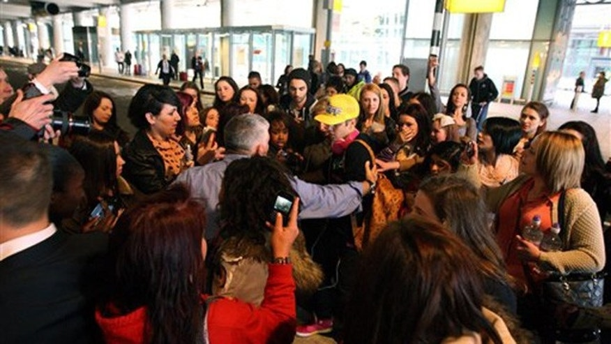 April 23, 2012: Canadian singer Justin Bieber wearing a yellow hat is greeted by fans as he arrives ahead of his album launch at Heathrow Airport, London.
