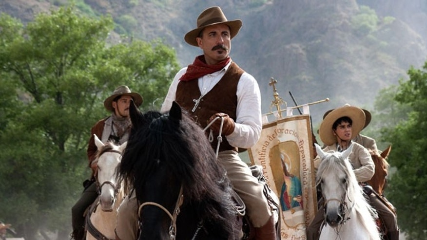 "In this undated image released by courtesy ARC Entertainment, center, Andy Garcia, and, right, Mauricio Kuri with flag, are seen in the film ""For Greater Glory."""