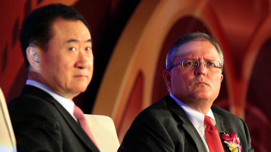 Gerry Lopez (R), chief executive of AMC Entertainment, listens to a question next to Wang Jianlin, president of Wanda Group, during a media conference after an official signing ceremony in Beijing May 21, 2012.