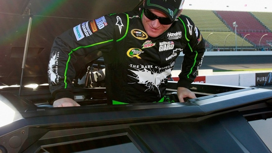BROOKLYN, MI - JUNE 14: Dale Earnhardt Jr., driver of the No. 88 Diet Mtn Dew/The Dark Night Rises Chevy, climbs inside the iconic Batman Tumbler at Michigan International Speedway on June 14, 2012 in Brooklyn, Michigan. (Photo By Geoff Burke/Getty Images for Mountain Dew)