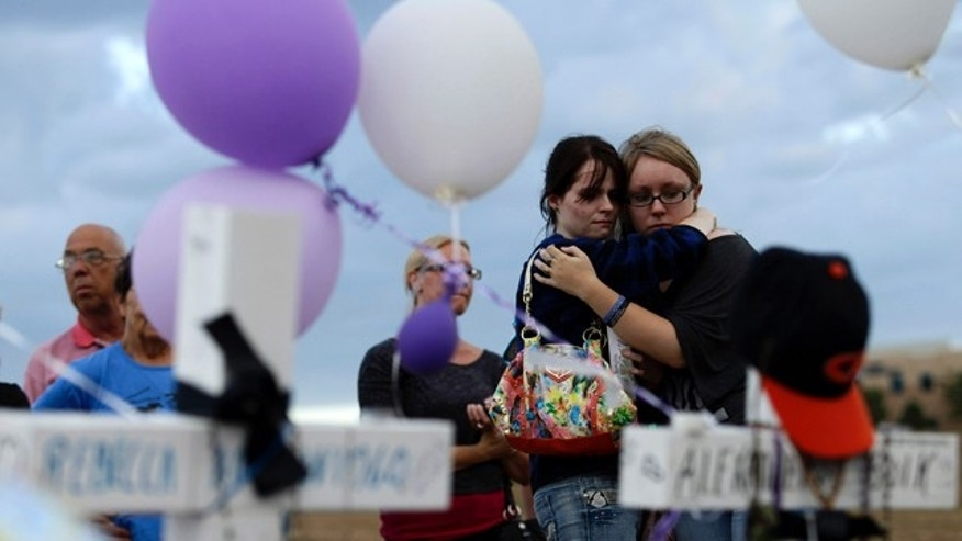 July 23, 2012:  Shelby Mahoney (2nd-R), 18, and Brittney Riddlebaugh (R), 19, both of Westminster, Colorado, embrace at at the makeshift memorial built across the street from the Century 16 theater  in Aurora, Colorado.