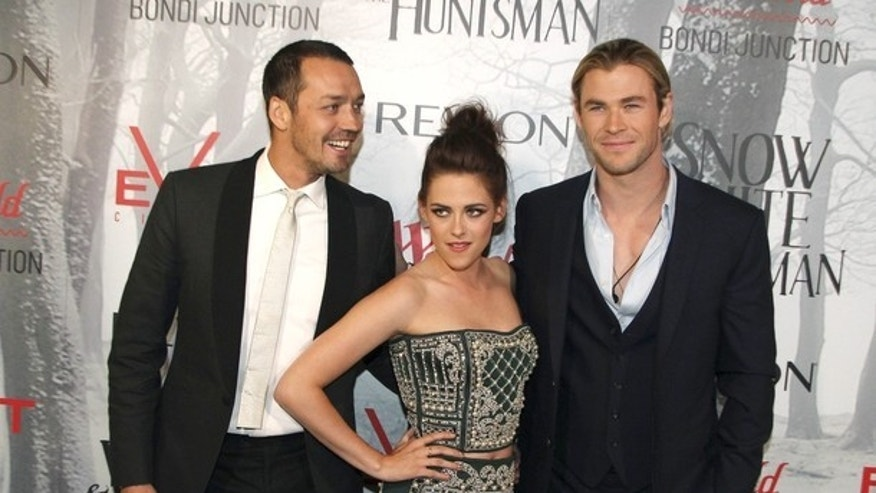 Actors Kristen Stewart, center, Chris Hemsworth, right, and director Rupert Sanders arrive on the red carpet for the premiere of Snow White & the Huntsman in Sydney, Australia, Tuesday, June 19, 2012. (AP Photo/Rob Griffith)