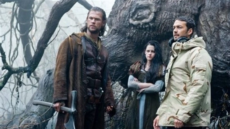 "This film image released by Universal Pictures shows actors Chris Hemsworth, from left, Kristen Stewart and director Rupert Sanders on the set of ""Snow white and the Huntsman."""