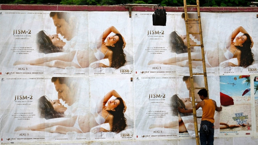"A man pastes the posters of Bollywood film ""Jism 2'"" outside a cinema hall in Bangalore, India, Thursday, Aug. 2, 2012. ""Jism 2"" stars a hard-core porn actress, and it does have that pesky title. But it is not a porn movie. Bollywood is certainly not ready for that. The film, which will be released across India on Friday, is pushing the ever-widening sexual boundaries enjoyed by many in urban India. (AP Photo/Aijaz Rahi)"