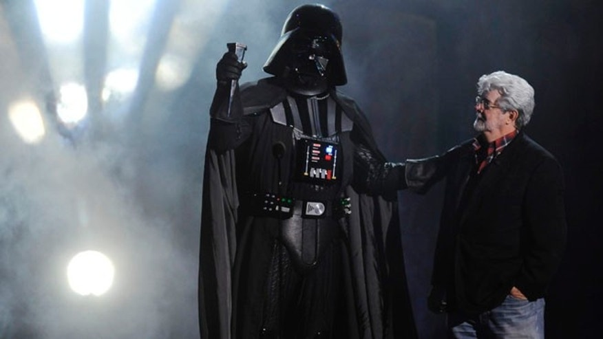 "Oct. 15, 2011: In this file photo, ""Darth Vader"" accepts the Ultimate Villain award from ""Star Wars"" creator George Lucas during the 2011 Scream Awards, in Los Angeles."