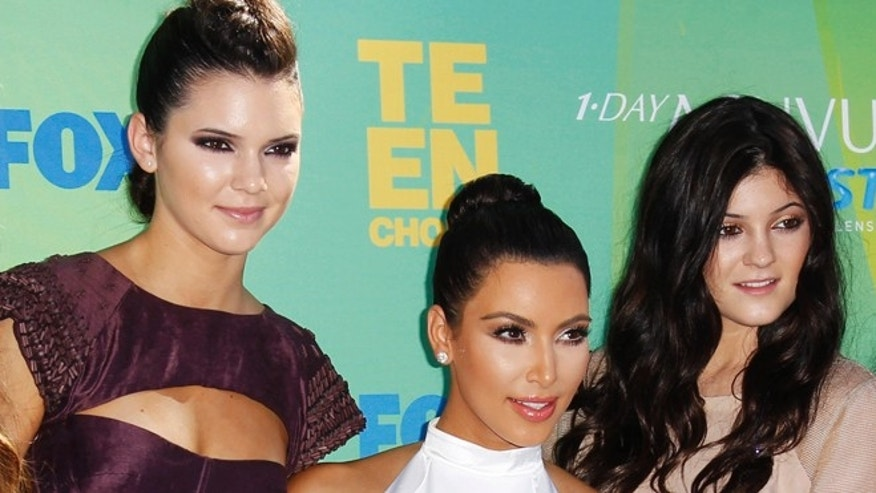 Kendall Jenner, Kim Kardashian and Kylie Jenner pose for a picture.