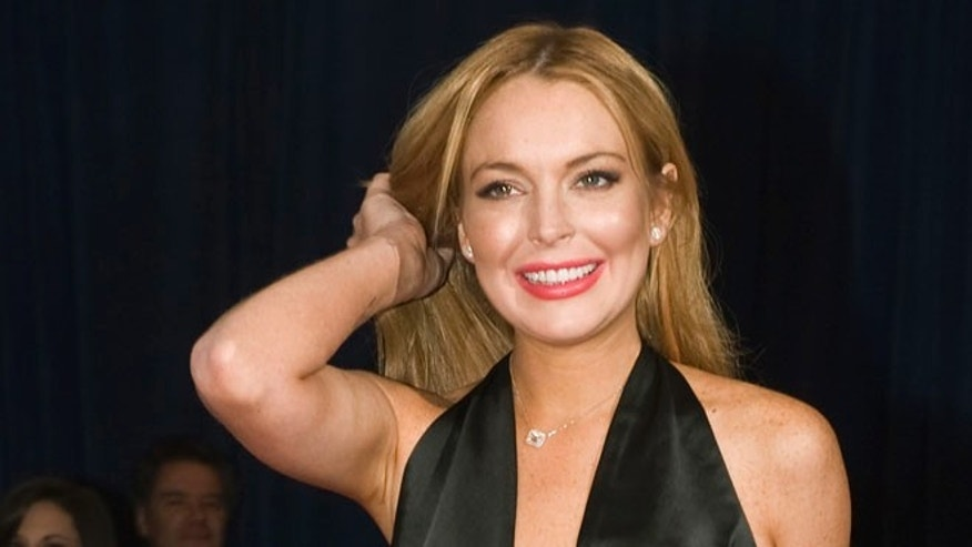 Actress Lindsay Lohan fixes her hair on the red carpet as she arrives for the annual White House Correspondents' Association Dinner at the Washington Hilton in Washington April 28, 2012.  REUTERS/Jonathan Ernst    (UNITED STATES - Tags: POLITICS ENTERTAINMENT)