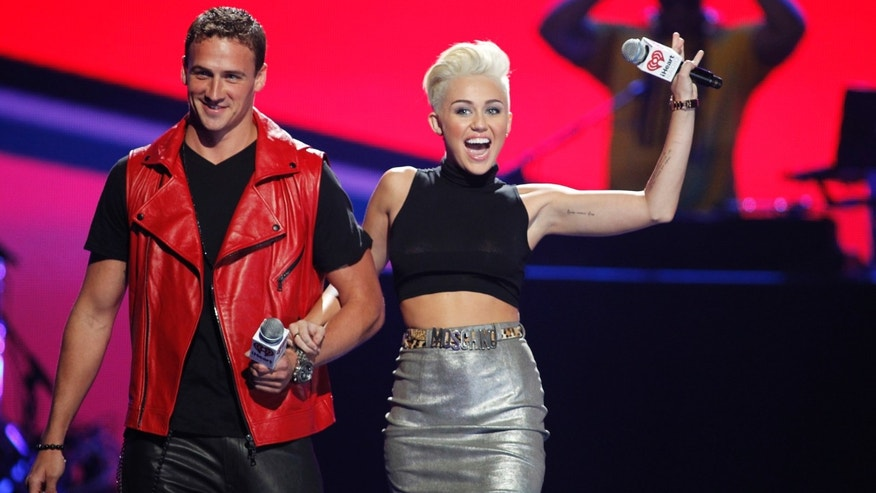Sept. 21, 2012: Olympic swimmer Ryan Lochte, left, and Miley Cyrus come onstage during the 2012 iHeart Radio Music Festival.
