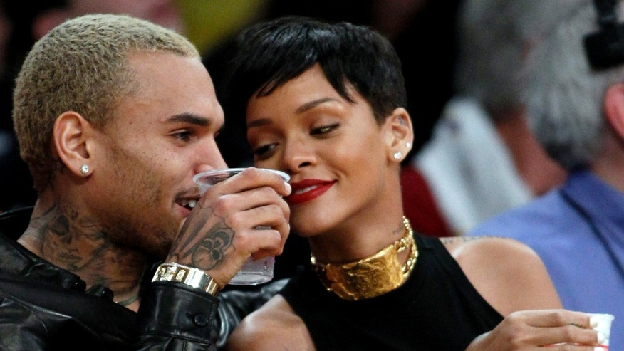 Chris Brown, left, and Rihanna attend an NBA basketball on Dec. 25, 2012.
