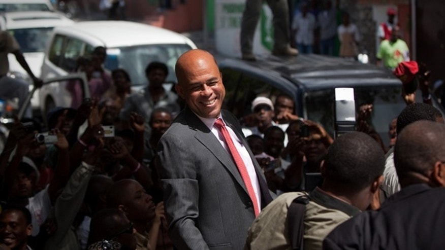 PORT-AU-PRINCE, HAITI - APRIL 5:  Haitian president-elect Michel Martelly greets supporters while returning to his car after a press conference the morning after the preliminary results of the campaign were announced April 5, 2011 in Port-au-Prince, Haiti.  Martelly took 67 percent of the vote against former first lady Mirlande Manigat.  (Photo by Allison Shelley/Getty Images)