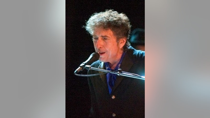 FILE - In this Aug. 26, 2006 file photo, Bob Dylan performs as the opening act of the Pawtucket Arts Festival at McCoy Stadium, in Pawtucket, R.I. Rock legend Bob Dylan was treated like a complete unknown by police in a New Jersey shore community when a resident called to report someone wandering around the neighborhood. Long Branch business administrator Howard Woolley says a 24-year-old police officer apparently was unaware of who Dylan is and asked him for identification.   (AP Photo/Stew Milne, File)