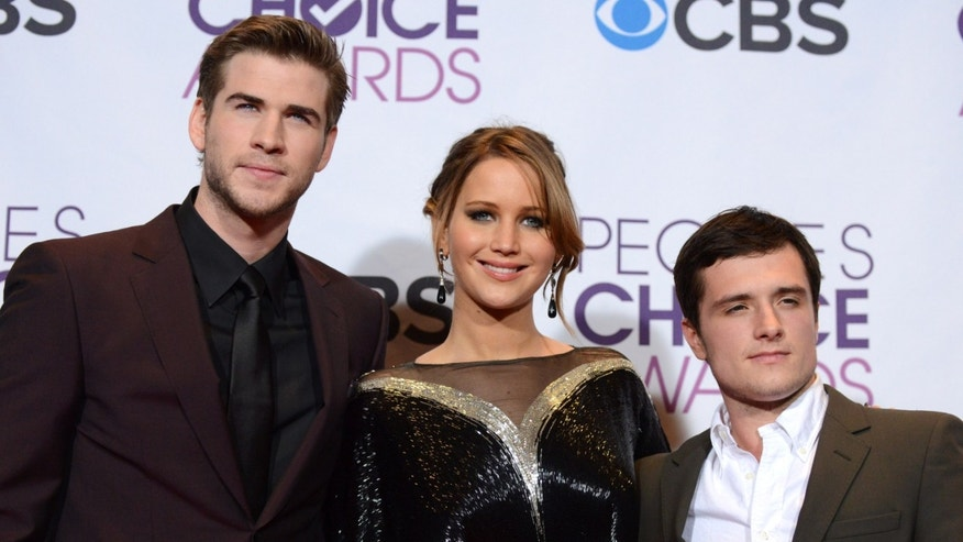 "Jan. 9, 2013:  Liam Hemsworth, Jennifer Lawrence and Josh Hutcherson, winners of the award for best movie for ""The Hunger Games,"" pose at the People's Choice Awards at the Nokia Theatre."