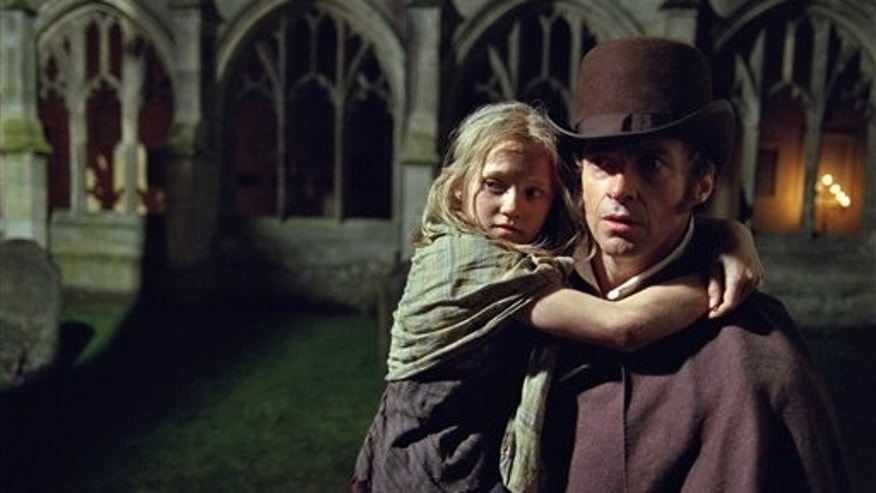 "This publicity film image released by Universal Pictures shows Hugh Jackman as Jean Valjean holding Isabelle Allen as Young Cosette in a scene from ""Les Miserables."""