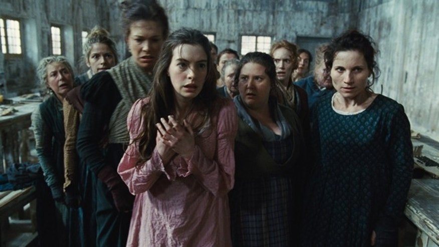 "This undated publicity photo provided by Universal Pictures shows Anne Hathaway, left, as Fantine, being thrown out of the factory in a scene from ""Les Miserables."""