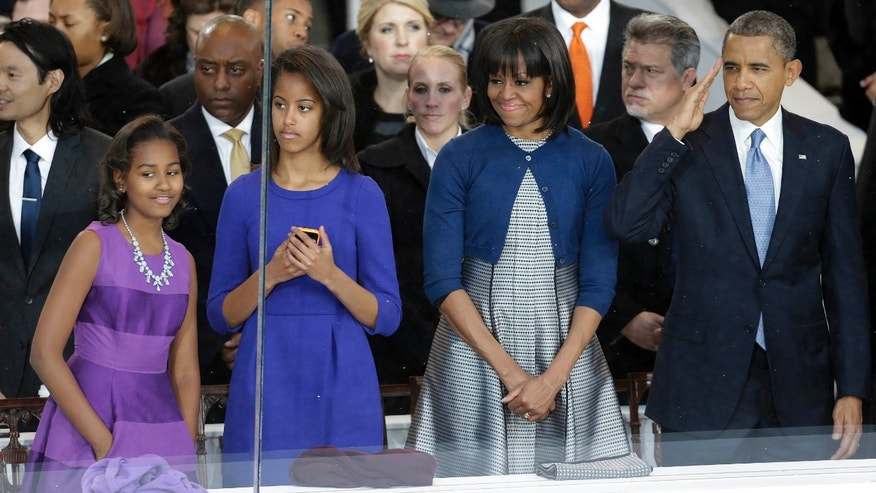 Jan. 21, 2013: President Barack Obama, right, and first lady Michelle Obama watch the Inaugural parade down Pennsylvania Avenue with their daughters, Sasha, left, and Malia, second from left, from the presidential box near the White House in Washington.