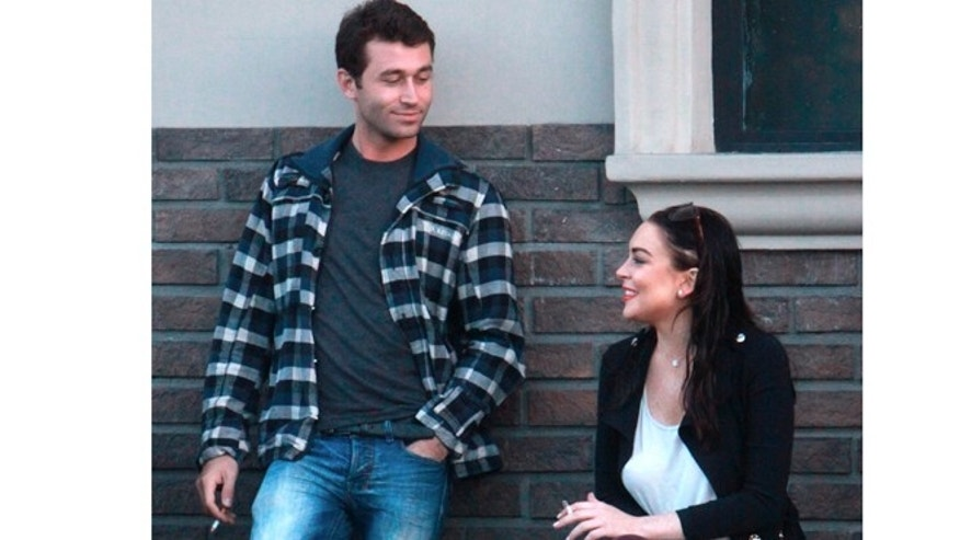 Lindsay Lohan smokes a cigarette besides her co-star James Deen.