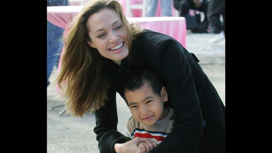 Actress Angelina Jolie  talks to her son Maddox at a news conference in New Orleans' Lower 9th Ward, Monday, Dec. 3, 2007. Jolie was attending the news conference where actor Brad Pitt announced his latest project to build affordable, environmentally friendly homes in the area devastated by Hurricane Katrina. (AP Photo/Bill Haber)