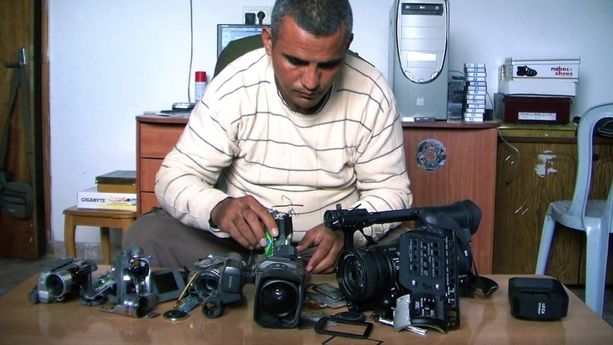 This undated publicity photo released by Kino Lorber, Inc. shows Co-director Emad Burnat with his five broken cameras.