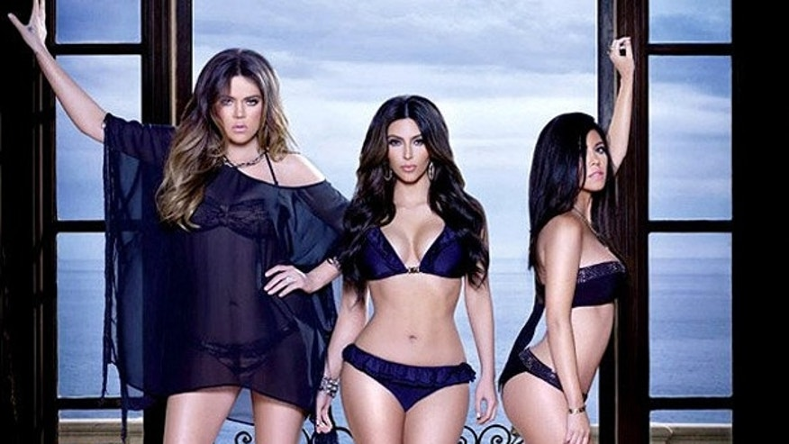 The Kardashian sisters pose in swimwear.