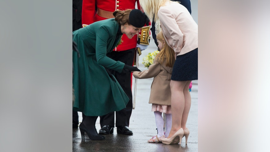 Britain's Kate the Duchess of Cambridge receives flowers from a little girl at the 1st Battalion Irish Guards' St Patricks Day Parade at Mons Barracks in Aldershot, England, Sunday, March 17, 2013.  Kate presenting the sprigs of shamrocks to the regiment Sunday, follows a century-old tradition inaugurated by Queen Alexandra, the wife of the then King, Edward VII back in 1901.  (AP Photo/Matt Dunham)