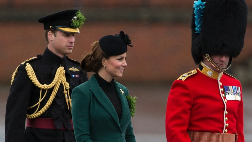 Britain's Prince William, left, and his wife Kate the Duchess of Cambridge walk with a member of the 1st Battalion Irish Guards during the St Patricks Day Parade at Mons Barracks in Aldershot, England, Sunday, March 17, 2013.  Kate presenting the sprigs of shamrocks to the regiment Sunday, follows a century-old tradition inaugurated by Queen Alexandra, the wife of the then King, Edward VII back in 1901.  (AP Photo/Matt Dunham)