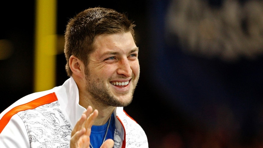 Former Florida Gators football star Tim Tebow waves to a crowd of fans.