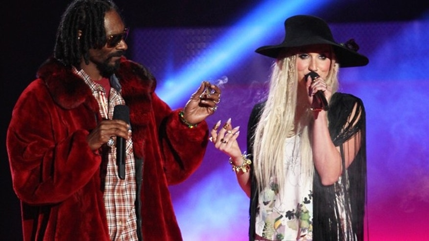 Snoop Dogg, left, and Ke$ha introduce Macklemore at the MTV Movie Awards in Sony Pictures Studio Lot in Culver City, Calif., on Sunday April 14, 2013.
