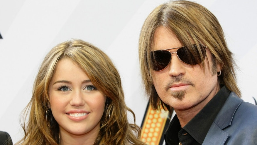 Miley Cyrus and father Billy Ray Cyrus arrive for their German film premiere 'Hannah Montana-The Movie' in Munich April 25, 2009.