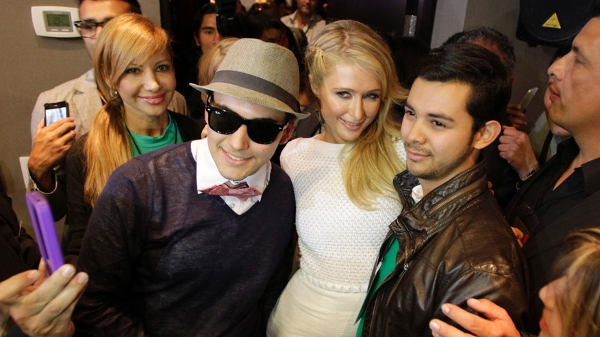 Paris Hilton poses with admirers in Bogota, Colombia, where she inaugurated her newest store. (AP/Fernando Vergara)